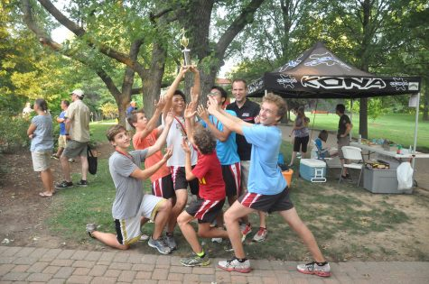 The varsity cross country team celebrates after winning their trophy at the Webster Warm-up on September 4.