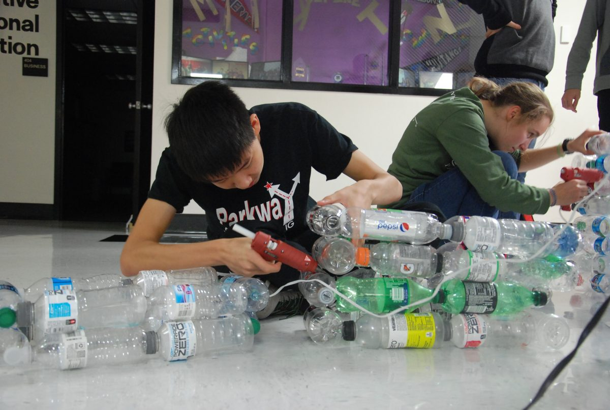 Junior Tony Chen and senior Emma Roberts attach layers of plastic bottles to stack onto Operation 350's Tower of Consumption on Dec. 4.