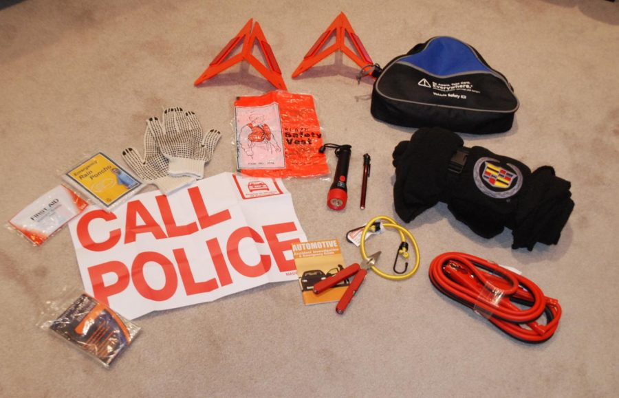 "An example of a pre-made emergency kit. Items included are jumper cables, a bungee cord, a multipurpose tool, a blanket, a safety vest, a pair of gloves, reflective cones, a ""Call Police"" sign, a small booklet for car care, a poncho, a first aid kit, and another emergency blanket."
