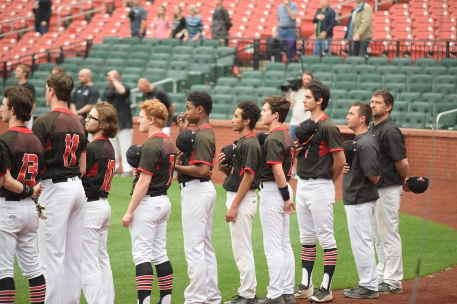 The team stands and looks at the American Flag while the National Anthem is played.