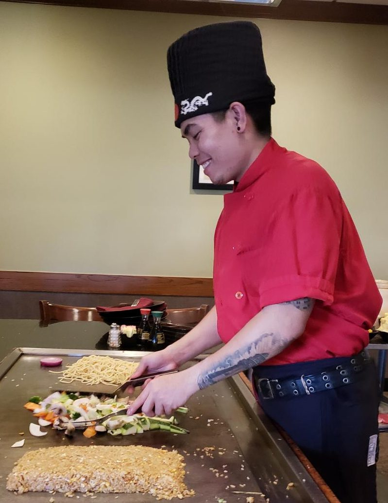 A hibachi chef smiles and laughs with guests as he prepares their meal. Photo taken by Brett Smith.