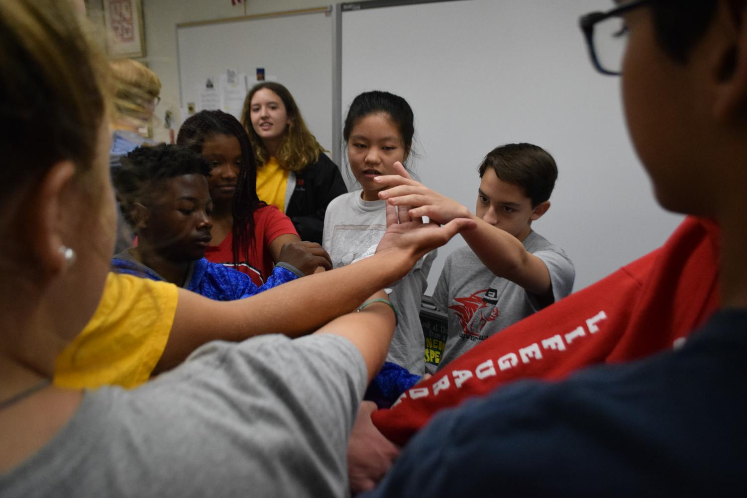 "Link Leader Chelsea Baird (11) looks on as (left to right) freshmen Amarion Lorthridge, Chelsea Smith, Lily Liu, and John Mendel participate in the ""Human Knot"" activity during AC Lab on Aug. 31. The goal is to link arms with someone and by the end of the game untangle the entire group so everyone is standing in a circle."