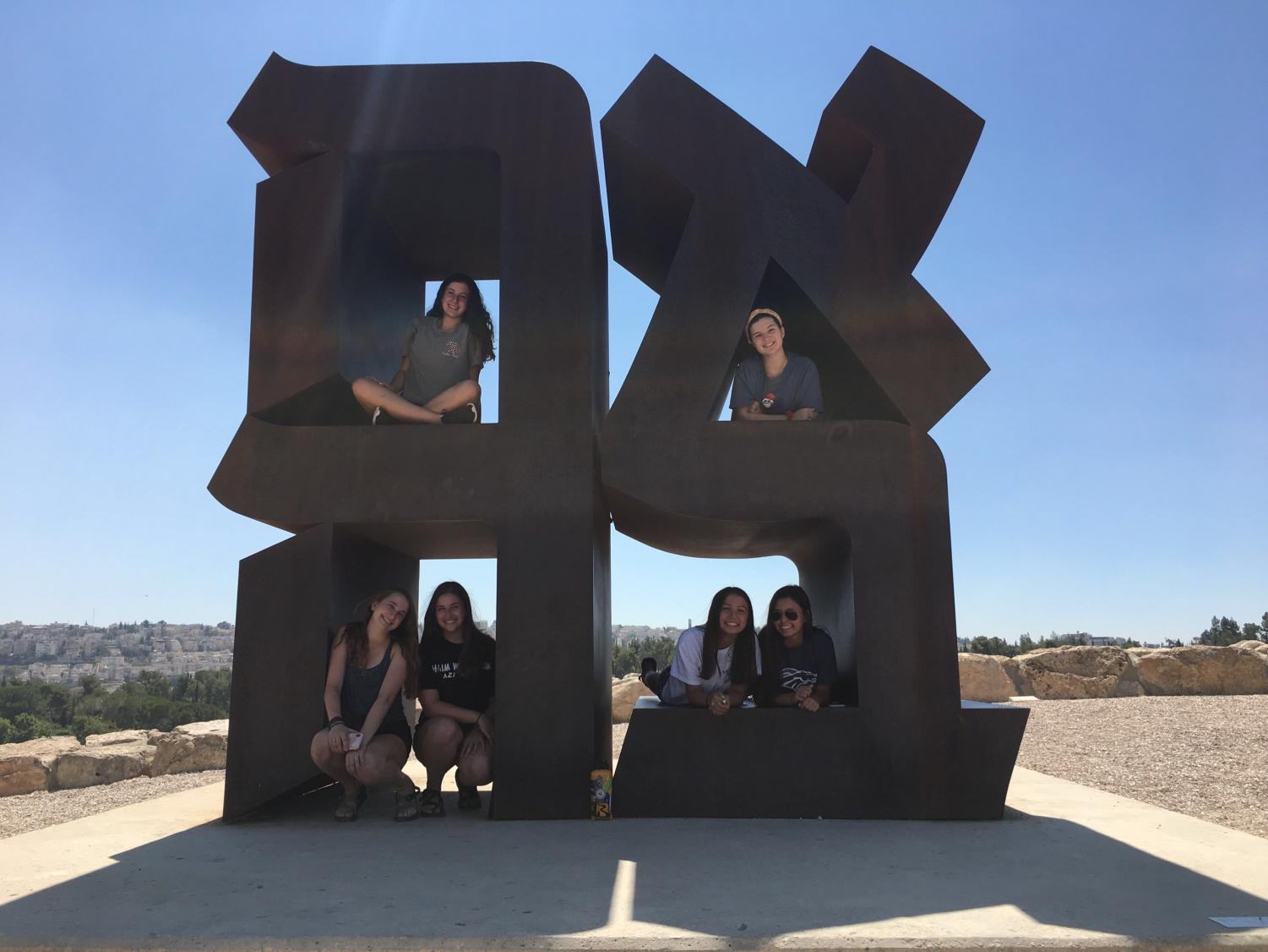 Junior Brette Gershenson and friends sitting on a statue at the Israeli art museum. Photo courtesy of Brette Gershenson.