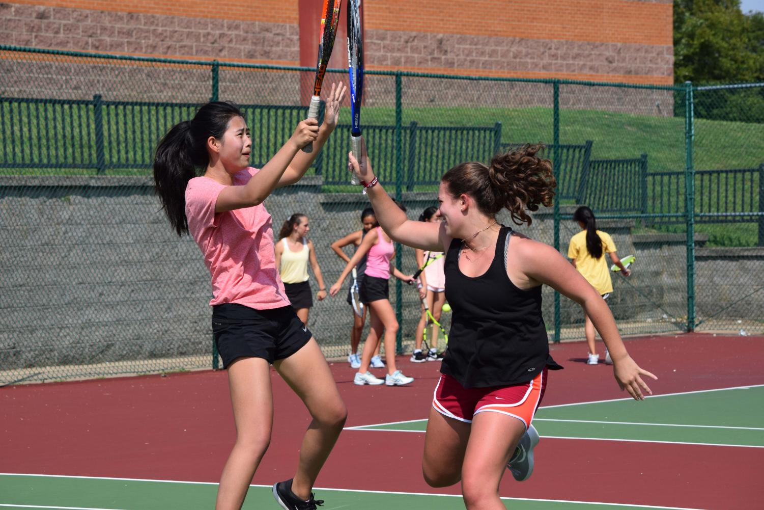Tamar Lerner and Irene Zhang hit racquets after winning a point at practice.