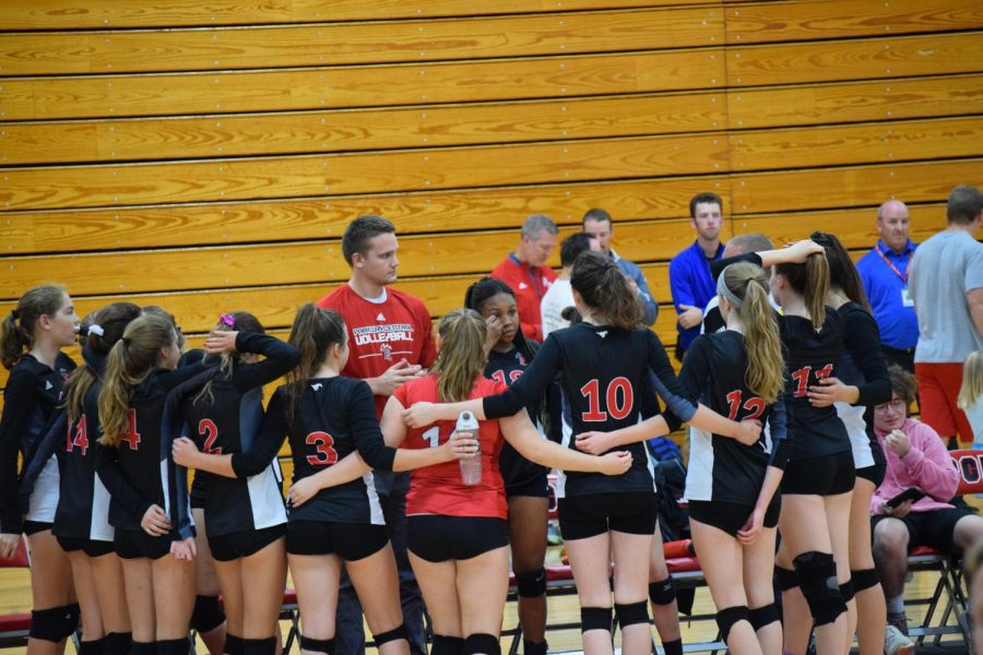 Assistant Coach Nathan Biggs talks to his team prior to the second set against Westminster.