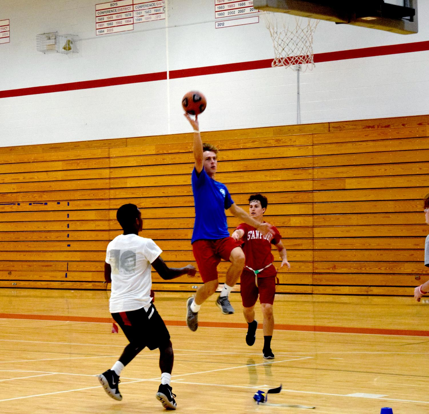 Junior Luke Schaefer jumps for a dunk while senior Jake Moritz pulls his flag during game of Gatorball, a combination of touch football, soccer, and football in competitive sports PE class.