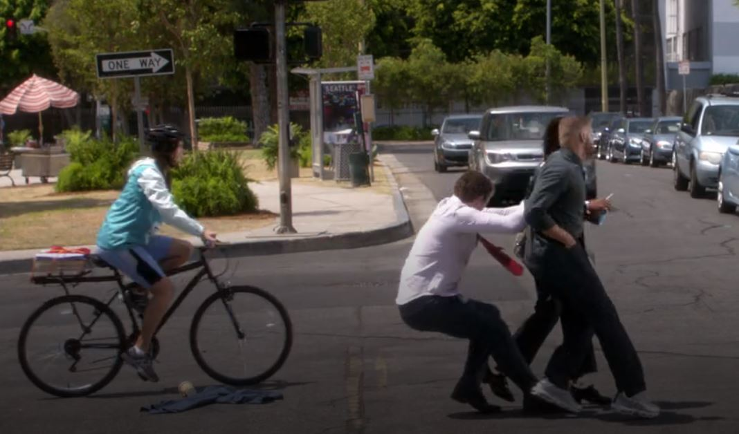 Deluca pulling Jackson and Maggie away from a speeding car, while a teenager on a bike passes  and is about to be hit.