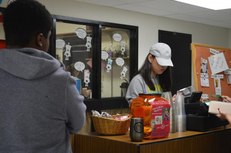 Cafe student manager YuTing Shi places an order sticker on a customers cup.