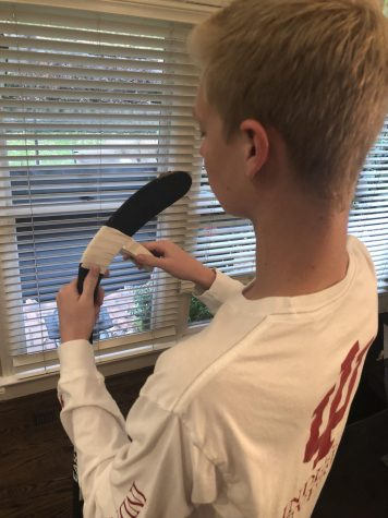 """Senior Jonathon Nathan tapes his hockey stick. """"No two people do it the same so I don't trust others to tape mine,' Nathan said. Photo by Avery Cooper."""