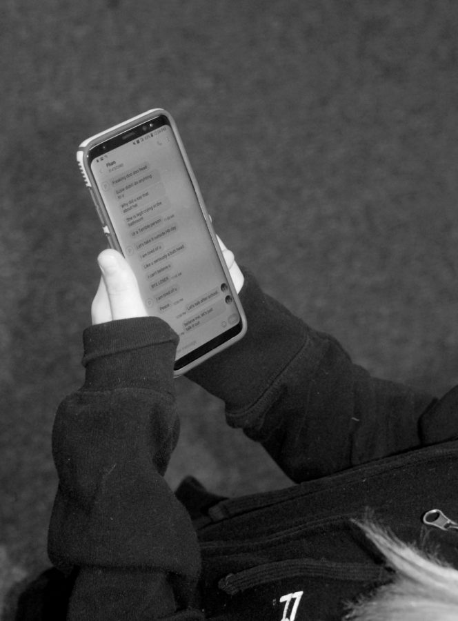 Student+checks+her+phone+for+messages.+Drama+can+be+started+through+texting.+Photo+by+Ryan+Pham