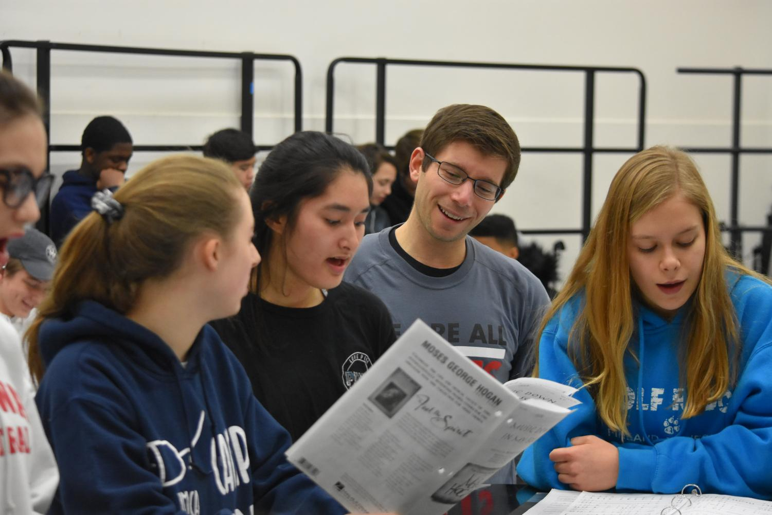 Choir teacher Ben Silvermintz helps freshmen Brianna Spaeth, Carine Heller, and Sophie Bain learn their part during Concert Chorale. It isn't unusual to hear Silvermintz belting the same notes as the girls. Photo by Trey Williams