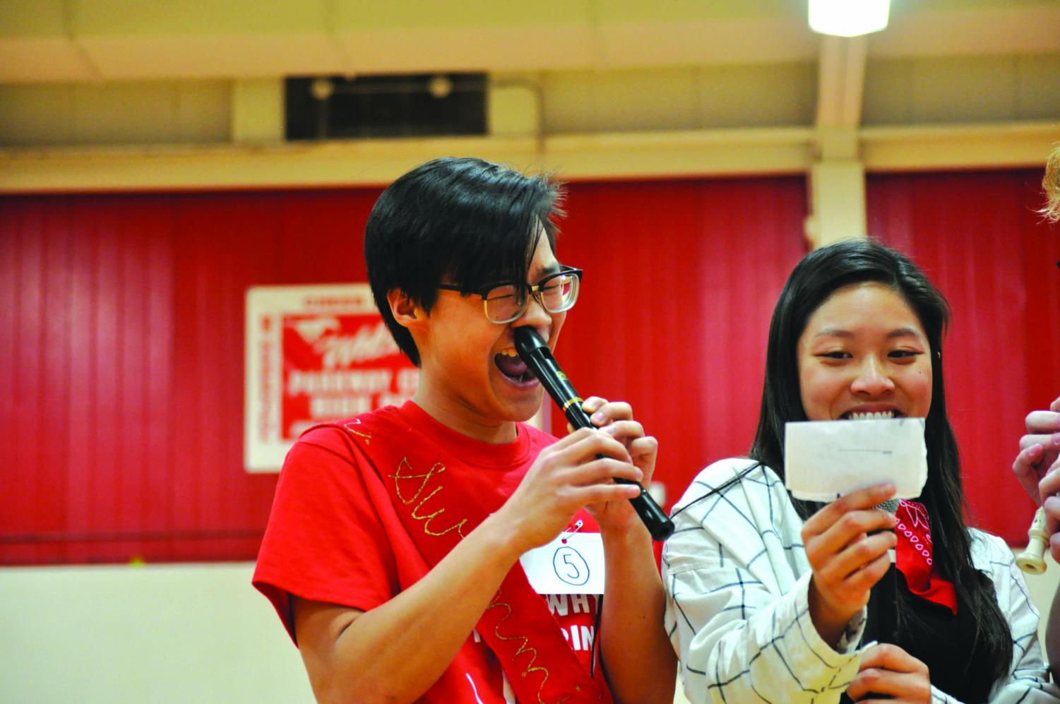 Left to right: Preston Chen plays the recorder with is nose while Tiffany Huang holds up notes.