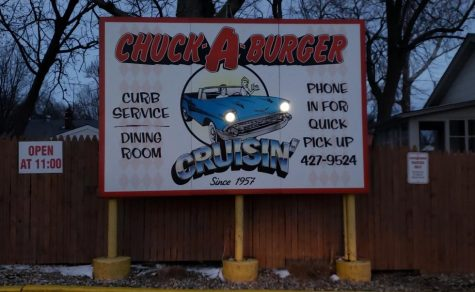 The restaurant sign for Chuck-A-Burger, with actual lit bulbs for the cars headlights.
