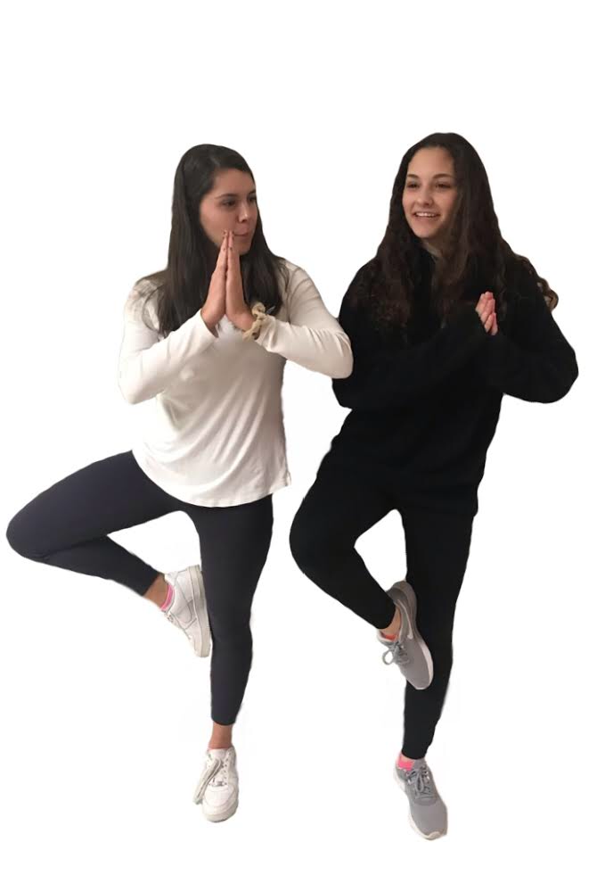 Sophomores Margaux Eubank and Julia Solomon practice the tree pose. Photo by Gabby Abowitz.