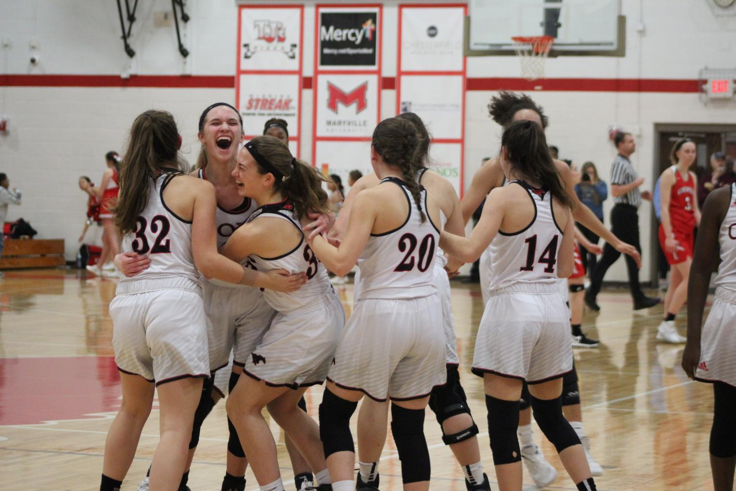 The girls varsity basketball team celebrates their district championship win on March 1, 2019 against Kirkwood.