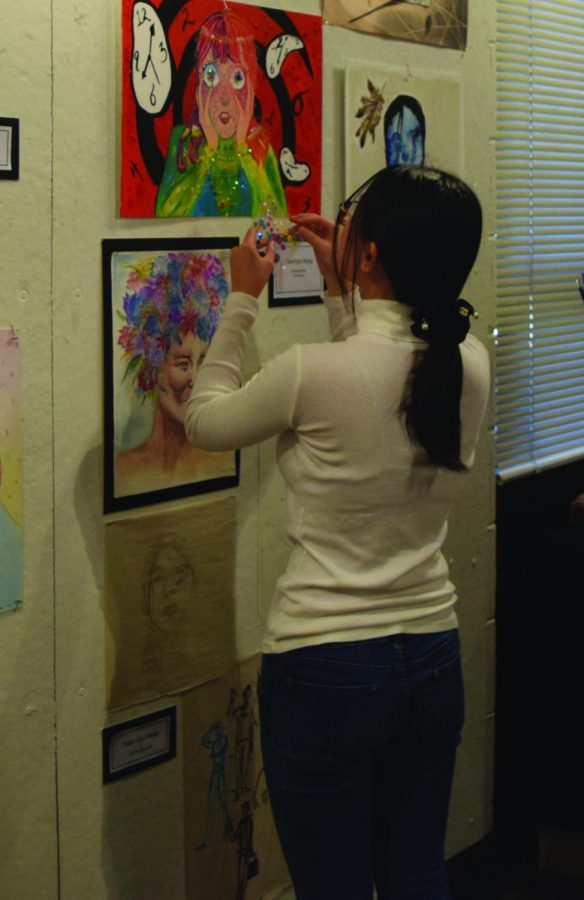 Junior art student Yeongyu Kang adds more to her art work during the school art show in December 2018. Photo by Athena Stamos