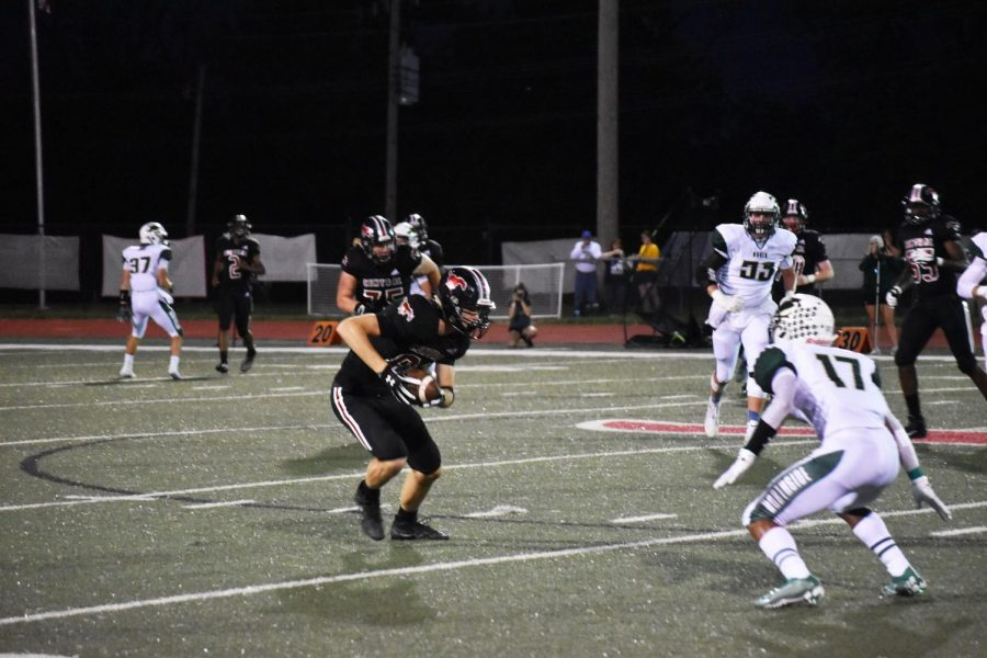 "Cam Roberts runs with the ball after making a reception in a game against Fort Zumwalt North on 9.13. ""I consider wide receiver my primary position even though there's only one punter on the field at a time, but there's always multiple wide receivers on the field,"" Roberts said. Photo by Christine Stricker."