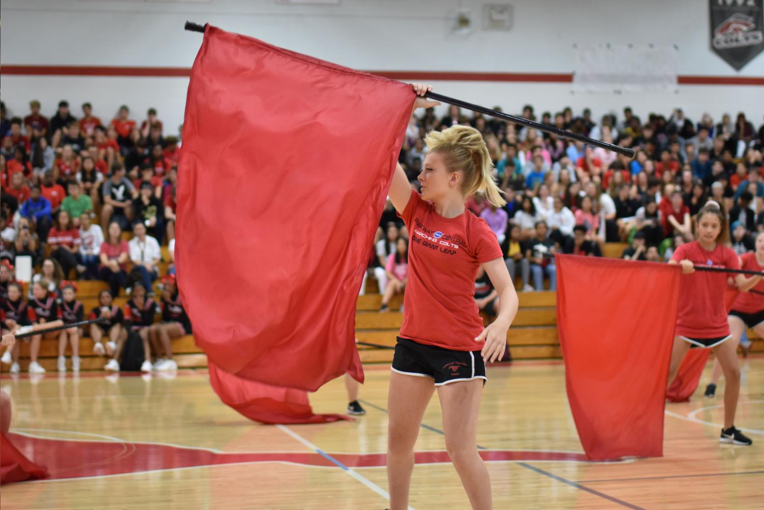 Senior Tristan Duggan spins her flag at the homecoming pep rally. Photo by Christine Stricker