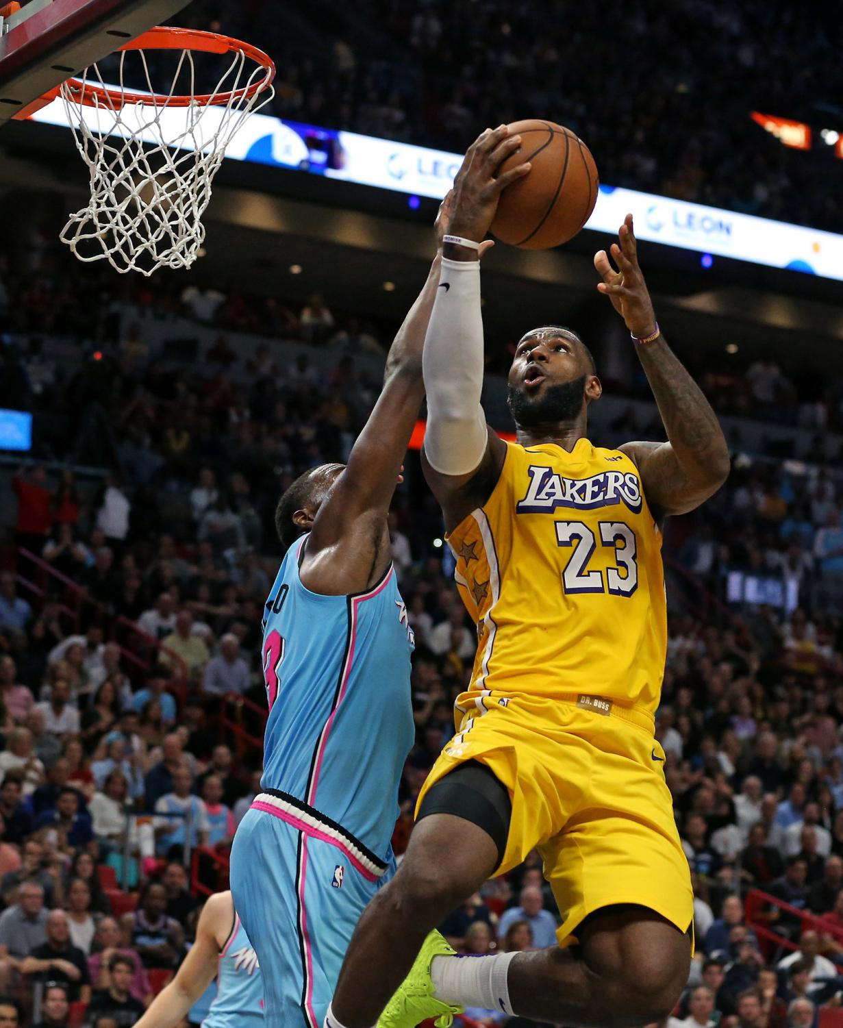 The Los Angeles Lakers' LeBron James (23) goes to the basket against the Miami Heat's Bam Adebayo in the fourth quarter at the AmericanAirlines Arena in Miami on Friday, Dec. 13, 2019. The Lakers won, 113-110. (David Santiago/Miami Herald/TNS)