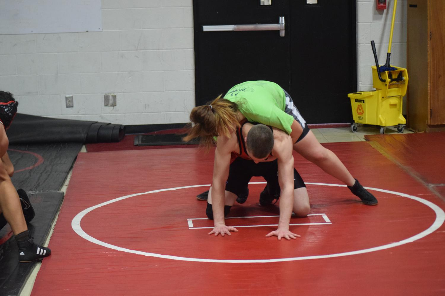 Freshman MJ Konieczny wrestling senior Joab Hackmann during practice. Due to Konieczny and Cox being in two different weight classes, the girls often have to wrestle other boys on the team. Photo by Alvi Lending.