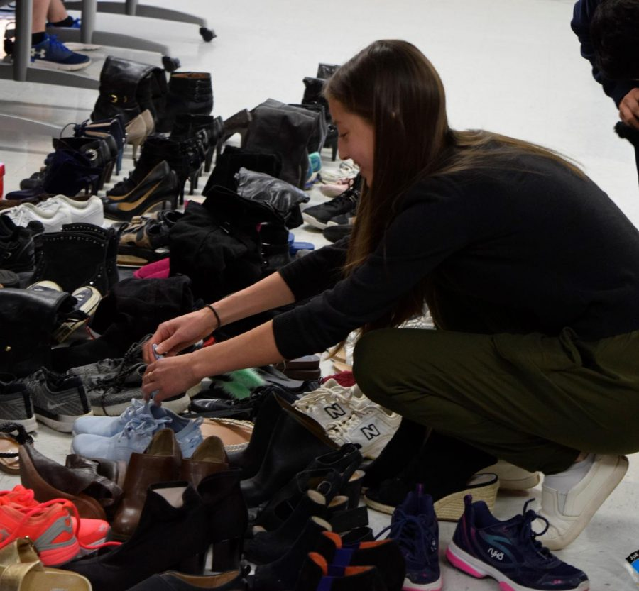 Senior Maria Vabson going through shoe donations collected by the senior class during Month of Giving. Month of Giving is held during November and it is when all the different grade levels compete to collect donations for their respective charities.