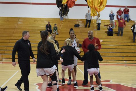 The girls basketball team rushes the floor to congratulate senior Jayla Kelley on her 1,000 point and 1,000 rebound accomplishments on Feb. 18 at the PCH gym.