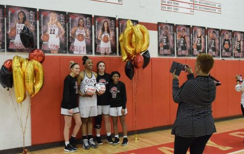 For her 1,000 point recognition on Feb. 18, senior Jayla Kelly poses under her senior poster with fellow seniors Brooke Hilton, Claudia Cooke and Kennedy Moore while Kelly's mother takes a picture. The recognition happened after the varsity game in which the Colts trounced Lindbergh.