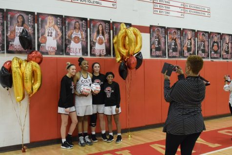 For her 1,000 point recognition on Feb. 18, senior Jayla Kelly poses under her senior poster with fellow seniors Brooke Hilton, Claudia Cooke and Kennedy Moore while Kelly