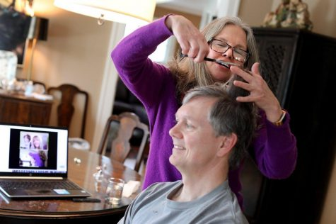 Mary Moore cuts the hair of her husband, Sam, with virtual guidance from Annah Davis, education director at Phia Concepts. Central Ohioans are taking haircuts into their own hands while salons and barbershops are shut down.