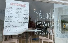 The outside of C. Oliver showing the menu and the black owned business sign. Photo taken by Gabby Abowitz.