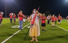 """The color guard and marching band perform together at a football game on Oct. 7, 2020. """"My favorite part would have to be waking up early in the morning with everyone else and just getting there early to watch the sun rise while doing a bunch of other stuff with the band and everything,"""" freshman Anastasia Lindholm said."""