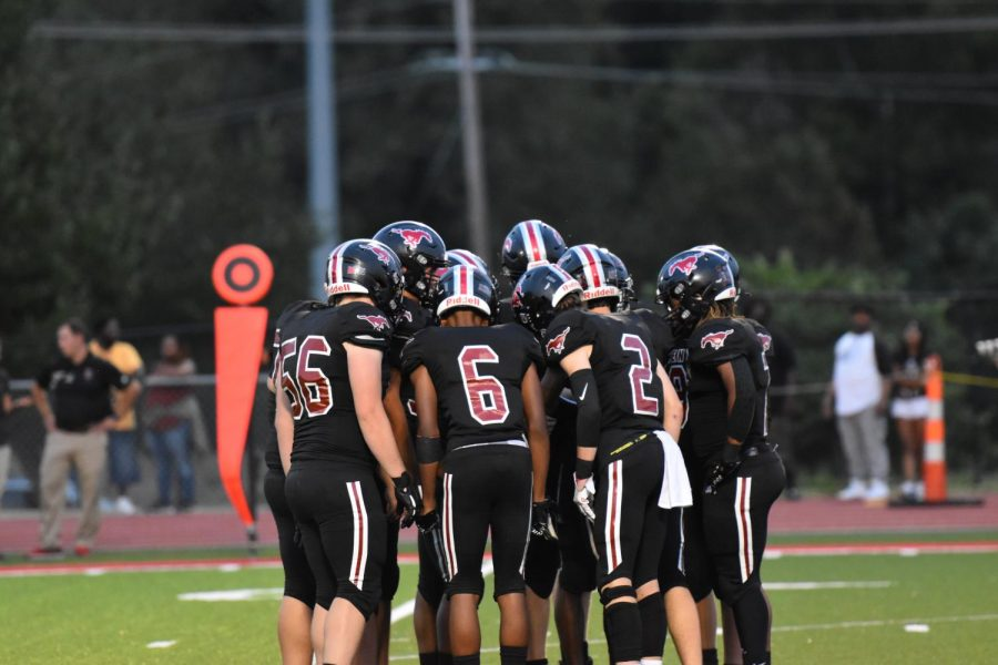The football team huddles together at their game against Rockwood Summit High School on Sept. 10. Photo by Kayelyn Tate.