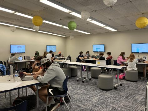 """Social studies students use the new library room. In addition to the tables circling the room, the tables in the center of the room are whiteboard tables that students can write on and flip over. """"All of the changes have to do with us trying to be responsive to the pandemic and to the different safety protocols,"""" Watson said. """"As everything has unfolded, we're working with our administration to try to keep everybody as safe as possible, while also trying to provide the best educational experiences possible, and so this year we've been able to reopen the libraries."""""""