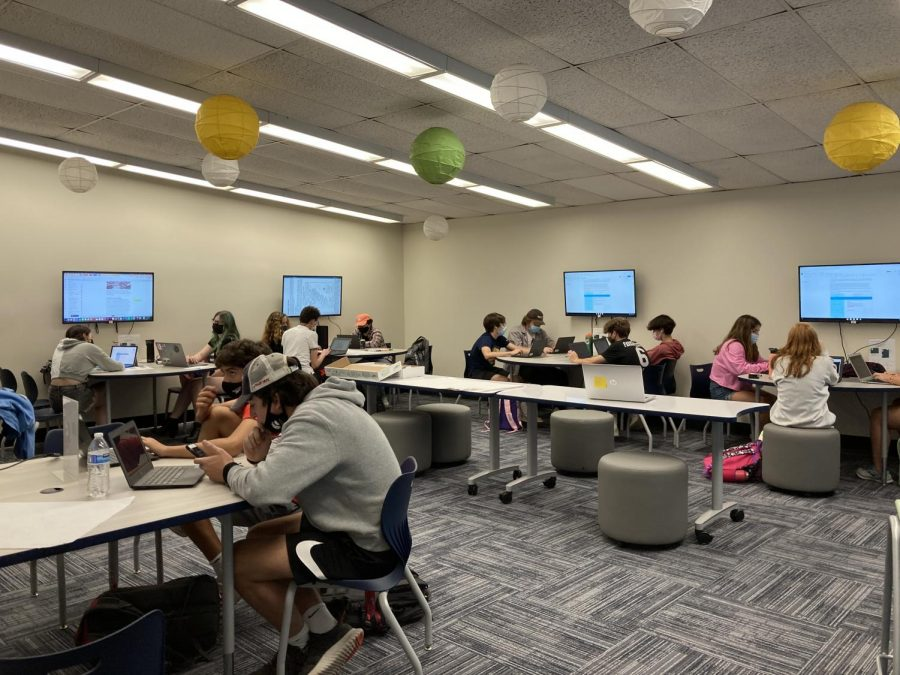 Social+studies+students+use+the+new+library+room.+In+addition+to+the+tables+circling+the+room%2C+the+tables+in+the+center+of+the+room+are+whiteboard+tables+that+students+can+write+on+and+flip+over.+%E2%80%9CAll+of+the+changes+have+to+do+with+us+trying+to+be+responsive+to+the+pandemic+and+to+the+different+safety+protocols%2C%E2%80%9D+Watson+said.+%E2%80%9CAs+everything+has+unfolded%2C+we%E2%80%99re+working+with+our+administration+to+try+to+keep+everybody+as+safe+as+possible%2C+while+also+trying+to+provide+the+best+educational+experiences+possible%2C+and+so+this+year+we%E2%80%99ve+been+able+to+reopen+the+libraries.%E2%80%9D+